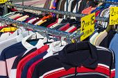 stock photo of flea  - Assorted second hand clothes on a flea market stall - JPG