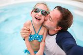 foto of swimming pool family  - Happy family father and his adorable little daughter at outdoors swimming pool making selfie - JPG