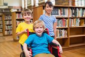 picture of pupils  - Cute pupils smiling at camera at the library at elementary school - JPG