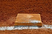 image of infield  - Chalk has spilled on either first or their base as the infield lines for fair or foul passes by - JPG