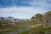 picture of curvy  - Curvy road towards some wooden houses in a small remote village in a mountain landscape in Jotunheimen National Park Norway - JPG