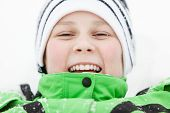 picture of beanie hat  - Happy laughing young boy wearing a knitted beanie hat lying in winter snow lifting his head to smile at the camera closeup of his face - JPG