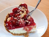 stock photo of crust  - Fork diving into a cheesecake with graham cracker crust and cherries - JPG