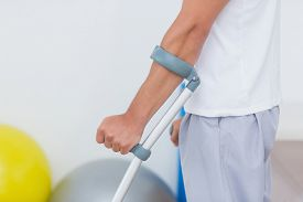 pic of crutch  - Patient standing with crutch in medical office - JPG