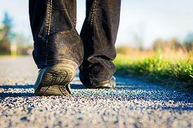 stock photo of street-walker  - man walking on the road alone in the sunset - JPG