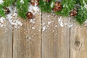 pic of snow border  - Christmas border with pine tree branches cones and snow on rustic wooden boards - JPG