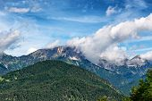picture of snow capped mountains  - High angle view of mountain covered with green fir trees - JPG