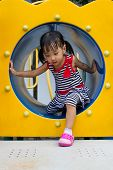 image of crawl  - Asian Chinese kid crawling on outdoor playground tube - JPG