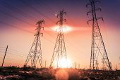 stock photo of power transmission lines  - Electrical power lines as sun sets in background - JPG