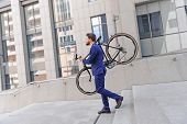 pic of vivacious  - Time to ride. Vivacious businessman holding his bicycle on his shoulders and looking straight while going down stairs. ** Note: Soft Focus at 100%, best at smaller sizes - JPG