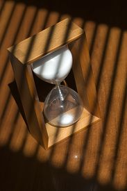 stock photo of jalousie  - One old fashiouned wooden hour glass clock with white sand standing on table top in jalousie shade vertical picture - JPG