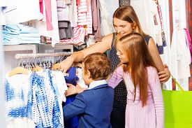 pic of women rights  - Woman with two children shopping together in the clothes store and choosing the right clothing item - JPG