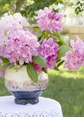 picture of flower vase  - Pink Rhododendrons in a handcrafted vase on a small table covered with a crocheted tablecloth - JPG