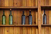 Cinco botellas de vino sin etiqueta en un estante de madera antiguo