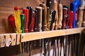 Row of old screwdrivers in a tool board of a garage