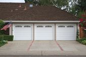 picture of garage  - Beige three ar garage with white doors and brick and red brick driveway - JPG