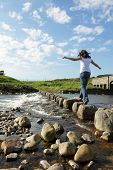 foto of stepping stones  - Young girl runs across stepping stones  to cross a stream - JPG