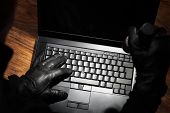 Burglar holding a torch stealing data from a laptop concept for computer security, corporate or iden