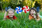 Five year old friends laying in a grass with colorful pinwheels