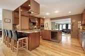 Kitchen with wood cabinets and bar chairs