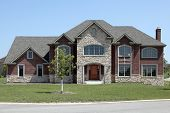 New construction brick home with stone entry