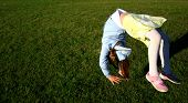 Girl in mid-air doing somersault on green grass