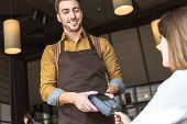 Happy Young Waiter Holding Payment Terminal While Client Inserting Credit Card poster
