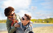 leisure and people concept - happy mixed-race teenage couple in sunglasses having fun over beach bac poster