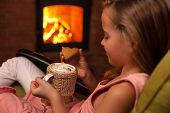 Young girl enjoying a cookie with a hot chocolate sitting by the fireplace - relaxing in the holiday poster