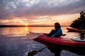 Two People In Kayaks On The River On The Scenic Sunset poster
