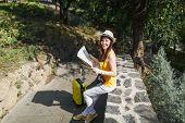 Young Joyful Traveler Tourist Woman In Yellow Clothes, Hat With Suitcase Hold City Map Sitting On St poster