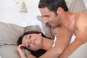 Man waking up his cranky wife