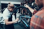 Professional Bike Repairman Fix Cycle In Workshop. Portrait Of Young Caucasian Man Wearing Apron Exa poster