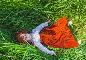Peace And Quiet. Doll With Red Hair Repose On The Green Grass. Peace Or Child Care Concept poster