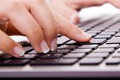 Close-up of secretary hand touching ENTER key on is laptop during work
