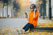 Cute Young Girl Listening Music In Headphones, Urban Style, Stylish Hipster Teen Sitting On A Sidewa poster