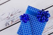 Christmas Gift Boxes On White Wooden Background. Blue Gift Boxes Tied With Blue Bow On Light Wooden  poster