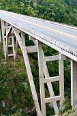 Tall bridge over a green tropical valley