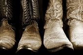 stock photo of boot  - Two pairs of well worn cowboy boots in high contrast light - JPG