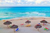 View from above of the cuban beach of Varadero with umbrellas and colorful recliner chairs at sunset