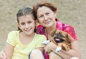 Adorable latin girl, her grandmother and the family dog in a park