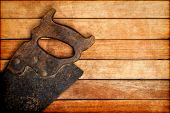 Old handsaw over a wooden boards background with space for text
