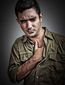 Dramatic portrait of a stressed man suffering from chest pain