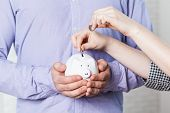 Inserting A Coin Into A Piggy Bank. Object. Close Up. Macro Photography poster