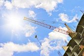 Building with elevating crane and sky with sun on background