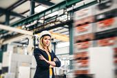 A Portrait Of An Industrial Woman Engineer Standing In A Factory, Arms Crossed. poster