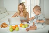 Mom Chooses A Cartoon For A Child During Breakfast. Young Mother Sitting At A Laptop Chooses A Carto poster
