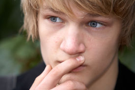 stock photo of teenage boys  - Teenage boy contemplating in city park close - JPG