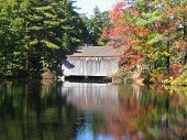 stock photo of covered bridge  - Covered bridge over a lake with fall foliage on adjoining trees - JPG