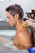 Side view of young man in pool receiving back massage with stress ball by a female